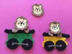 Finished crochet lion group on a pink background