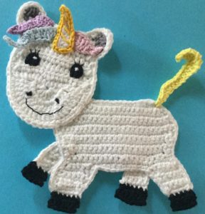 Crochet unicorn body with first tail piece