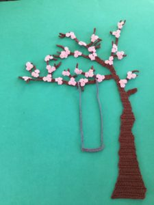 Finished crochet blossoms and swing blue background portrait