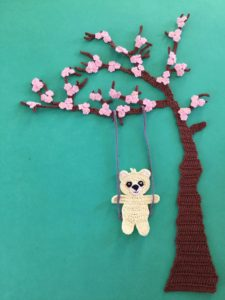 Finished crochet blossoms and swing blue background with teddy portrait