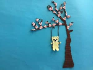 Finished crochet blossoms and swing for tree bright blue background with teddy landscape